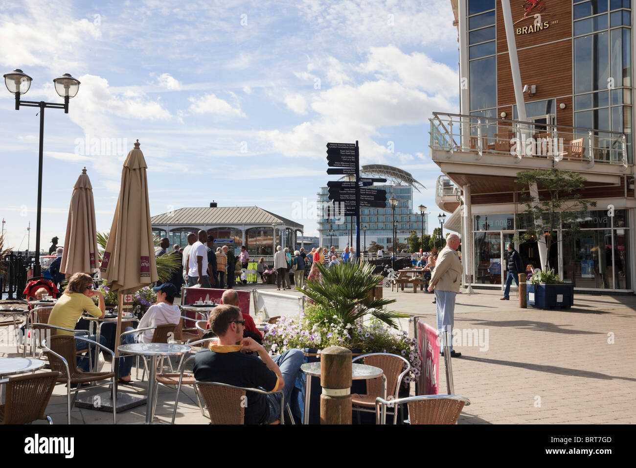 People sitting outside in pavement cafés on waterfront. Mermaid Quay, Cardiff Bay, Glamorgan, South Wales, - Stock Image