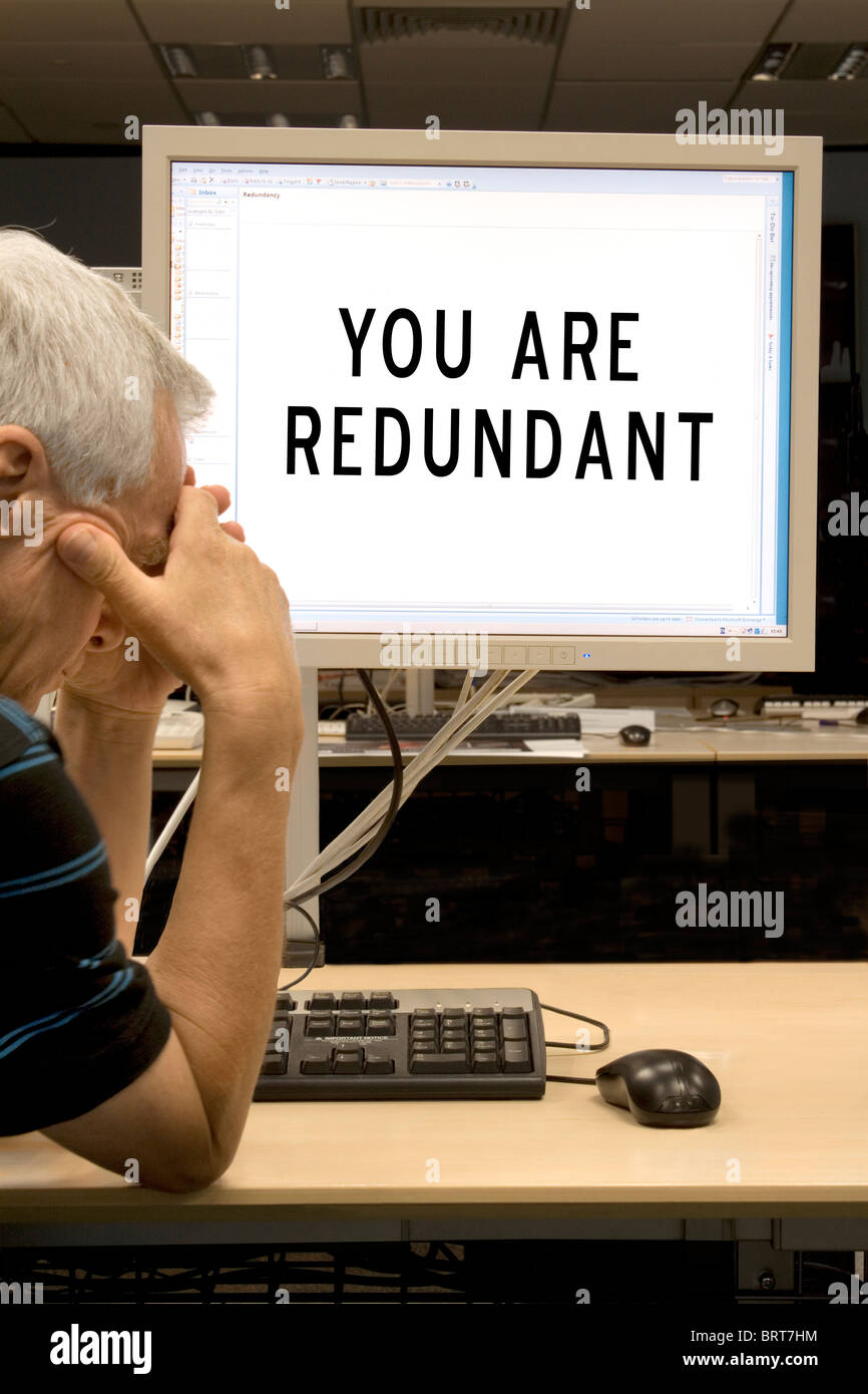 A man of approximately 60 years of age holds his head in his hands after being  made redundant by email while at - Stock Image