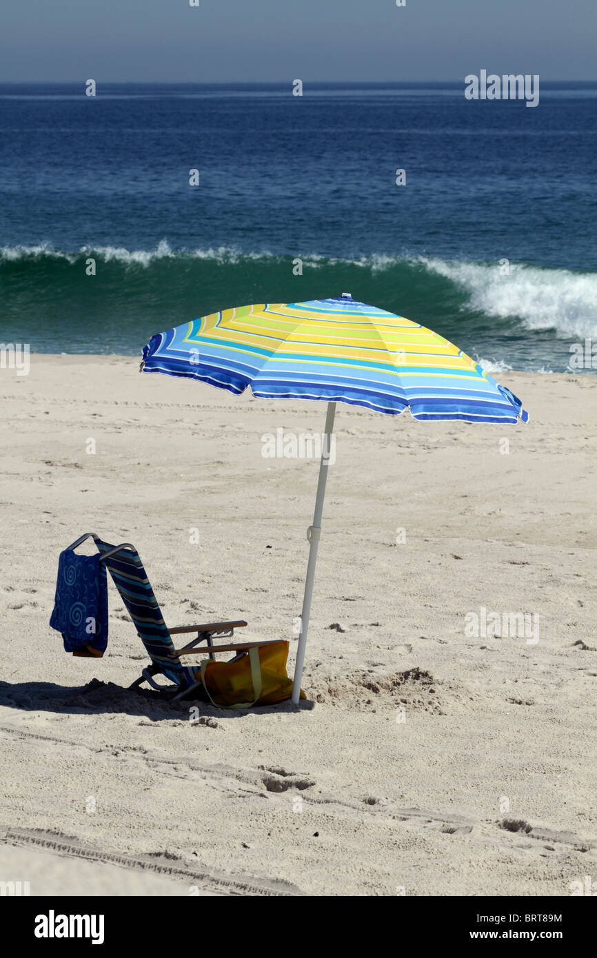 Beach umbrella in front of breaking wave. Lavalette, New Jersey, USA. - Stock Image