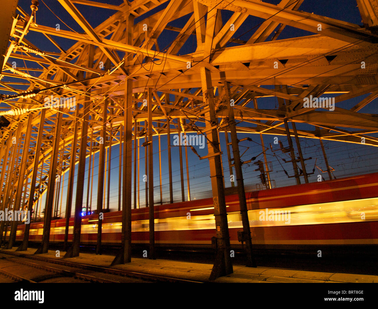 Train passing Hohenzollernbrucke railway bridge at night. Cologne, NRW, Germany - Stock Image