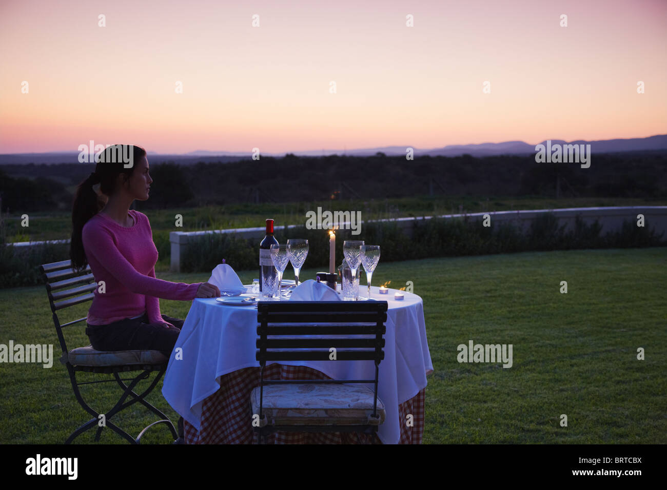 Woman sitting at table for dinner at River Bend Lodge, Addo Elephant Park, Eastern Cape, South Africa - Stock Image