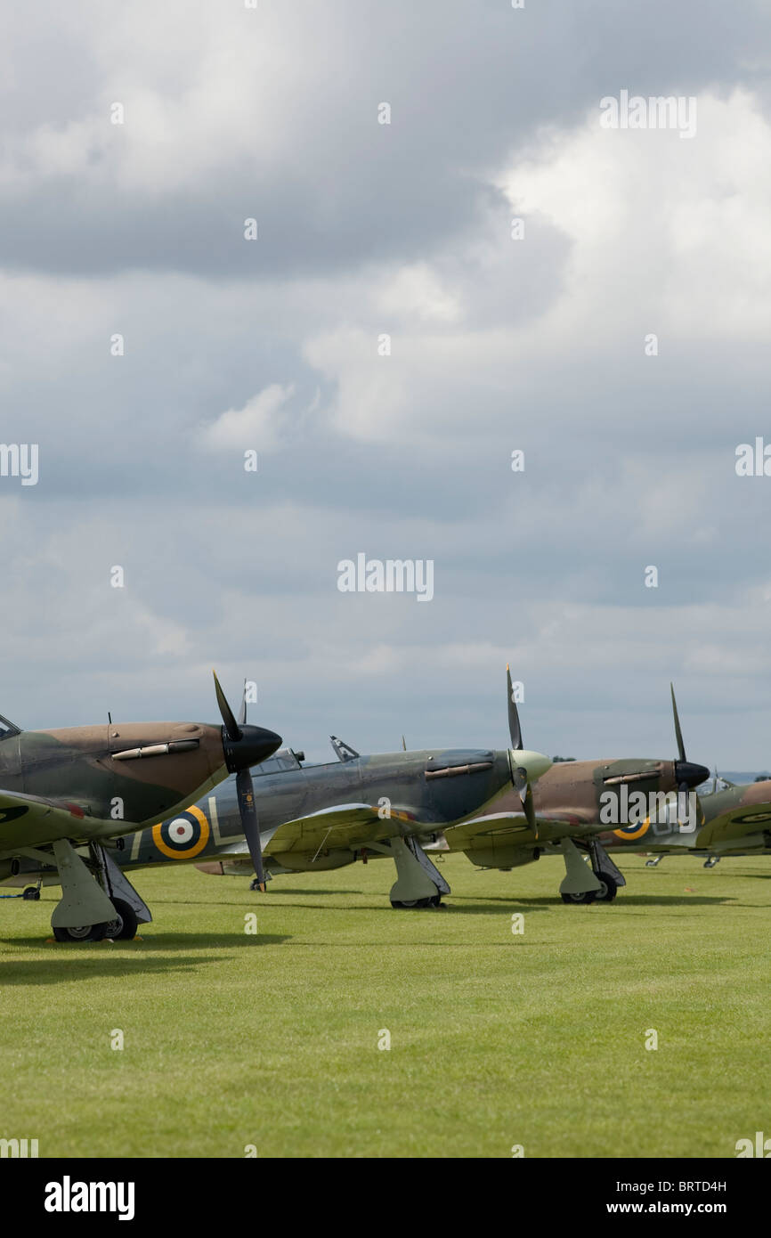 3 restored Hurricane aircraft lined up under a Cambridgeshire sky with a spitfire in the background - Stock Image