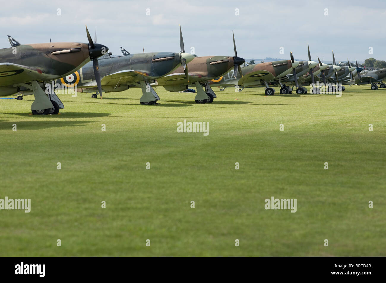 An impressive line up of 3 Hurricanes and 7 Spitfires on the grass in the sunshine - Stock Image