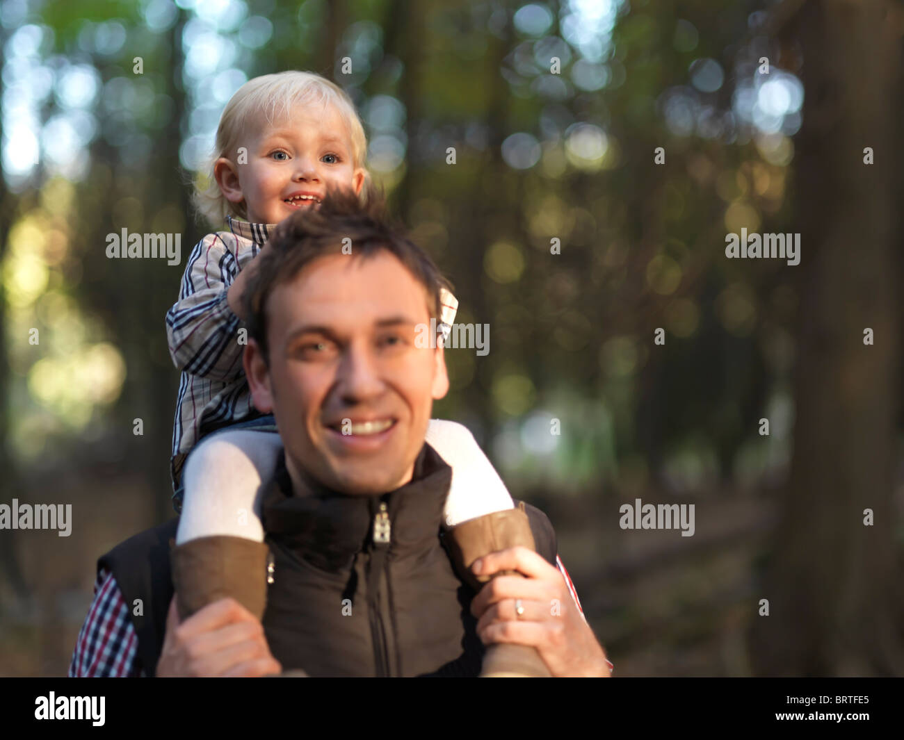 Little girl riding on her fathers shoulders in the nature. The focus is on the child. - Stock Image