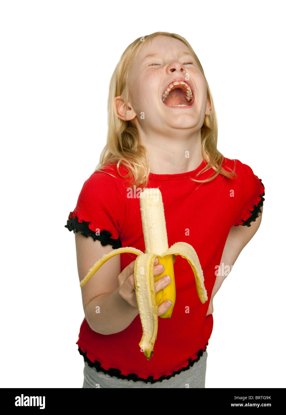 Young happy pretty caucasian girl eating a banana - Stock Image
