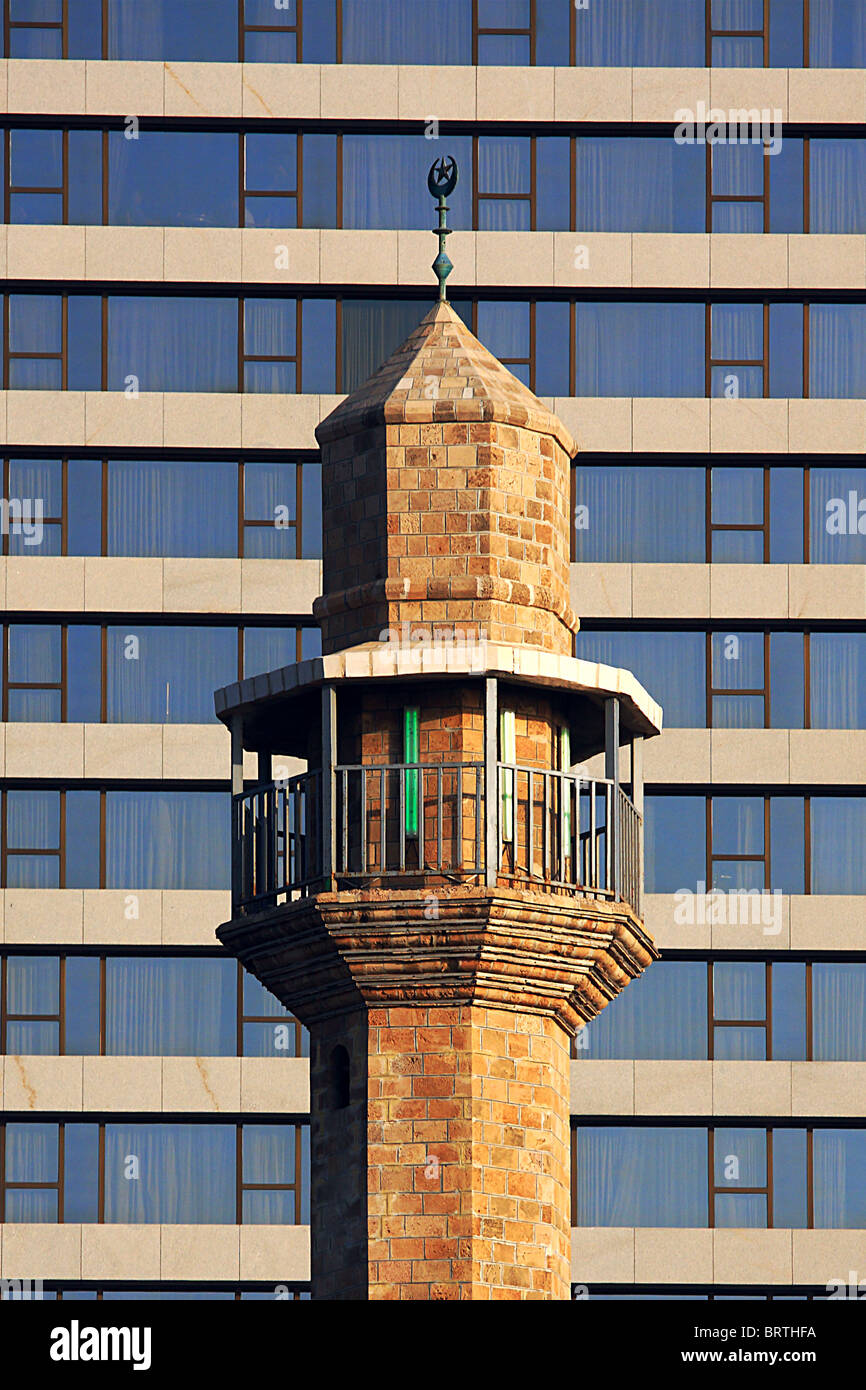 Old mosque against new modern building (hotel) in Tel-Aviv, Israel. - Stock Image