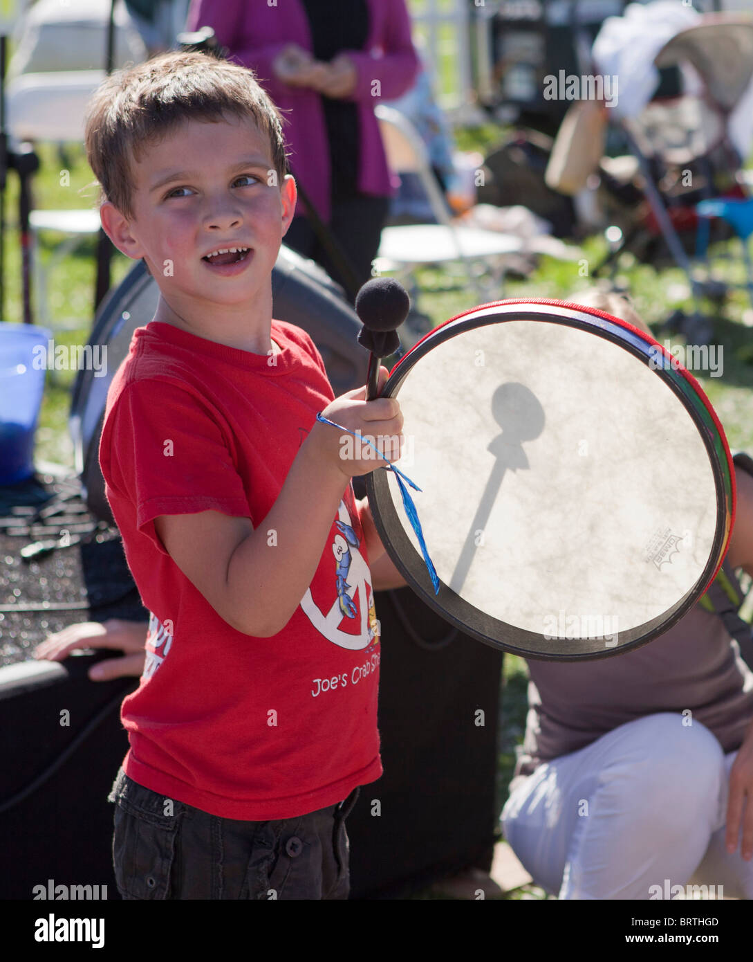 A young boy bangs on a drum at an outdoor music festival - Stock Image
