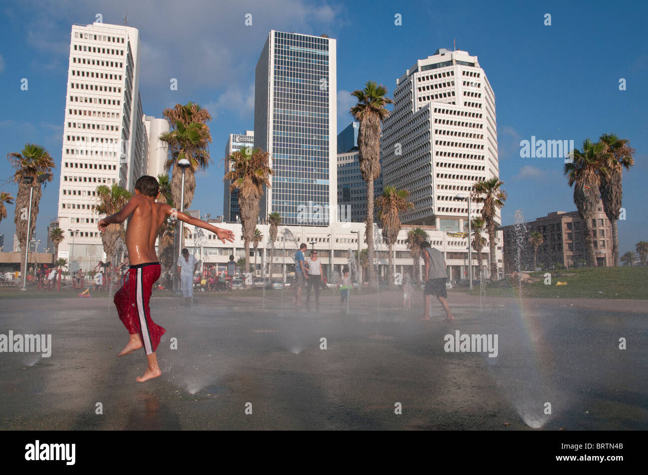 boy playing in urban fountain in front of textile compound. Tel Aviv. Israel - Stock Image