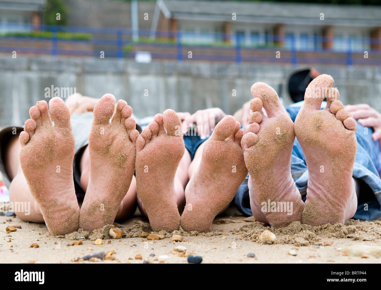 Families sandy feet on beach - Stock Image