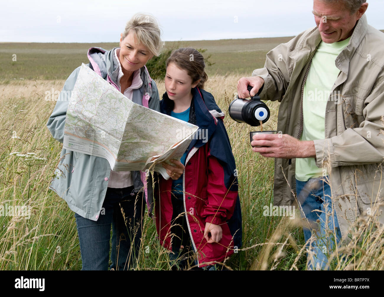 Seniors and granddaughter pause on walk - Stock Image