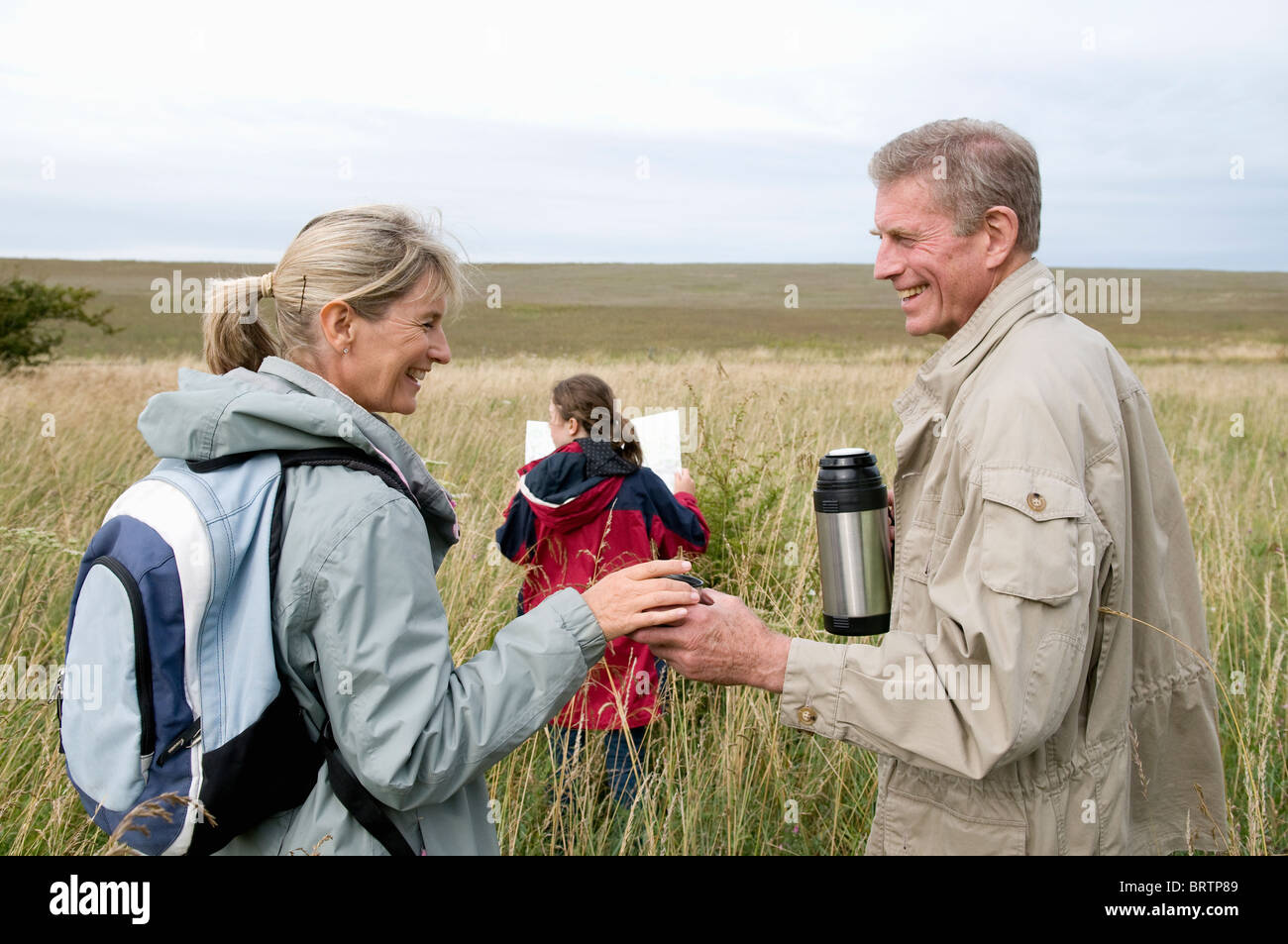 Seniors and grandchild pause on walk - Stock Image