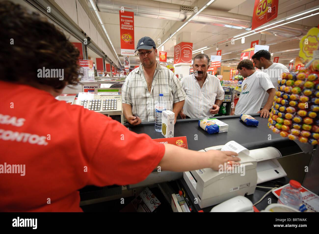 Man paying at supermarket checkout counter - Stock Image