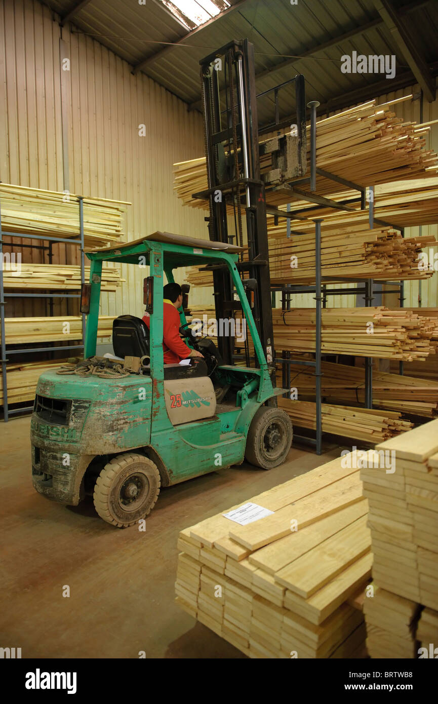 Man operating forklift truck to carry wood planks in a warehouse - Stock Image