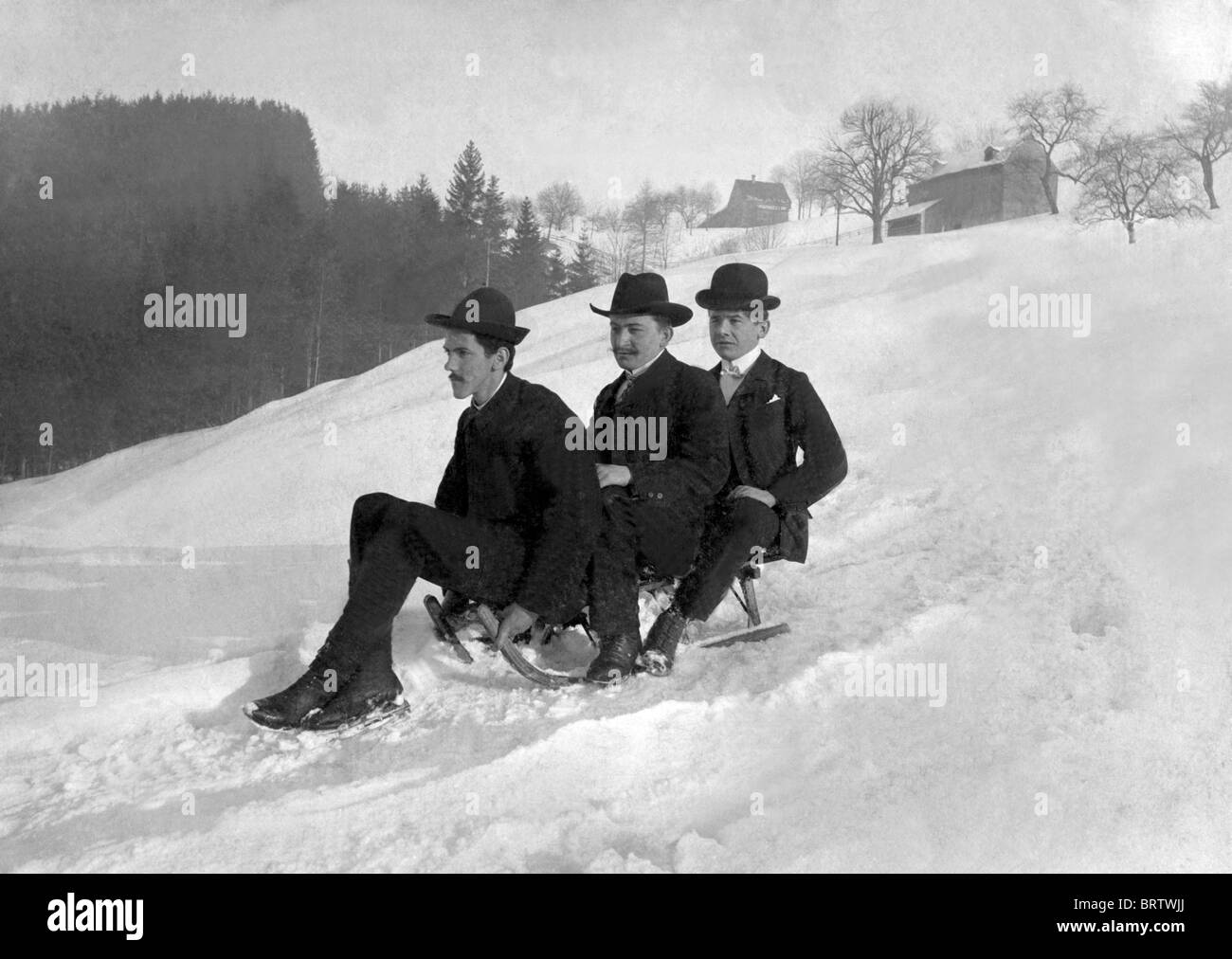 Three gentlemen riding a sled, historical image, ca. 1912 - Stock Image