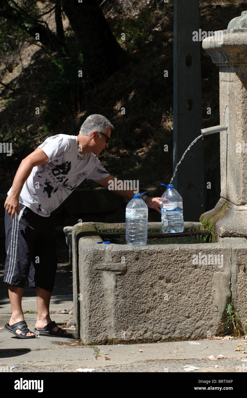 Man filling water bottles at a public fountain - Stock Image