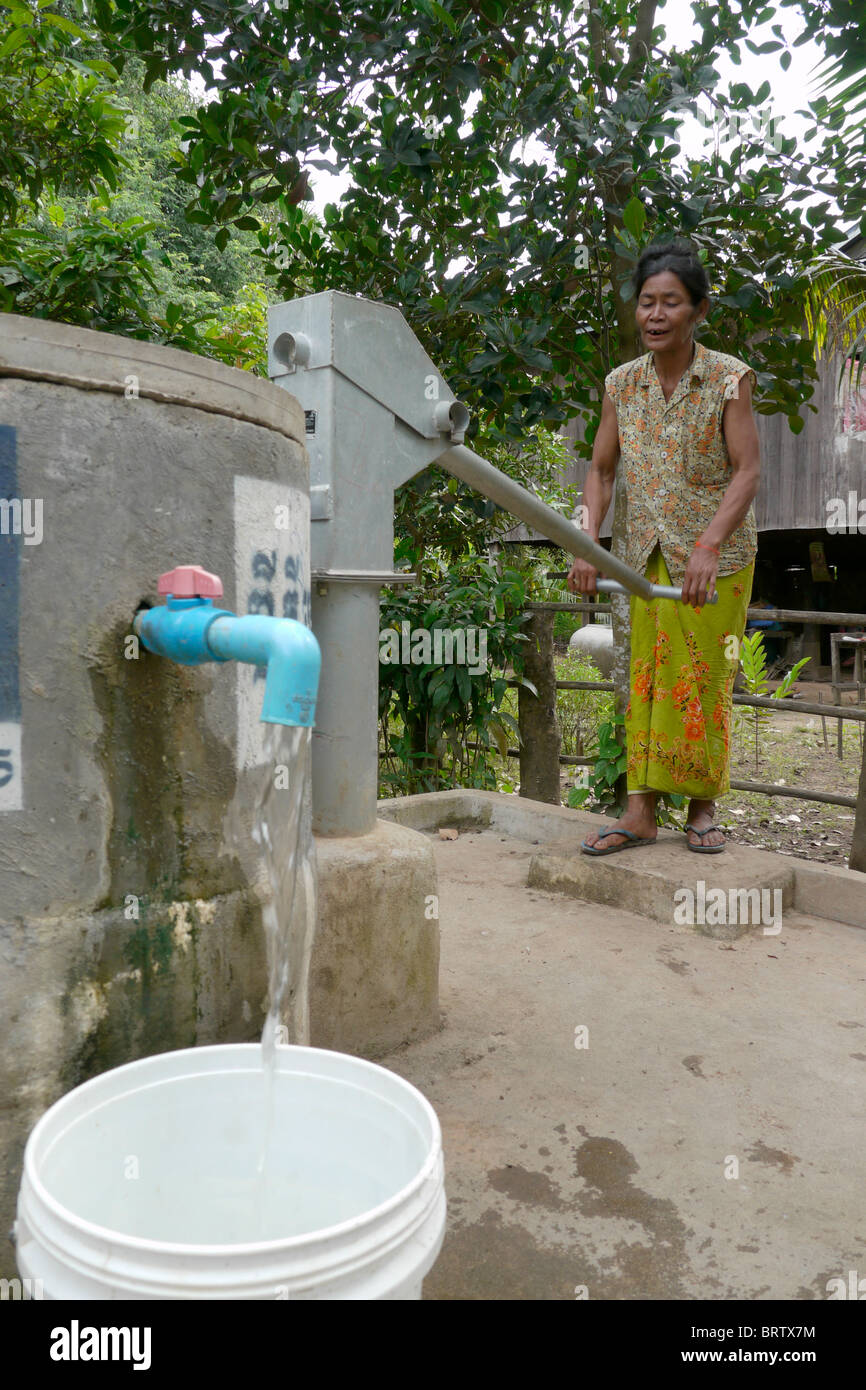 CAMBODIA  WOMAN PUMPING WATER - Stock Image