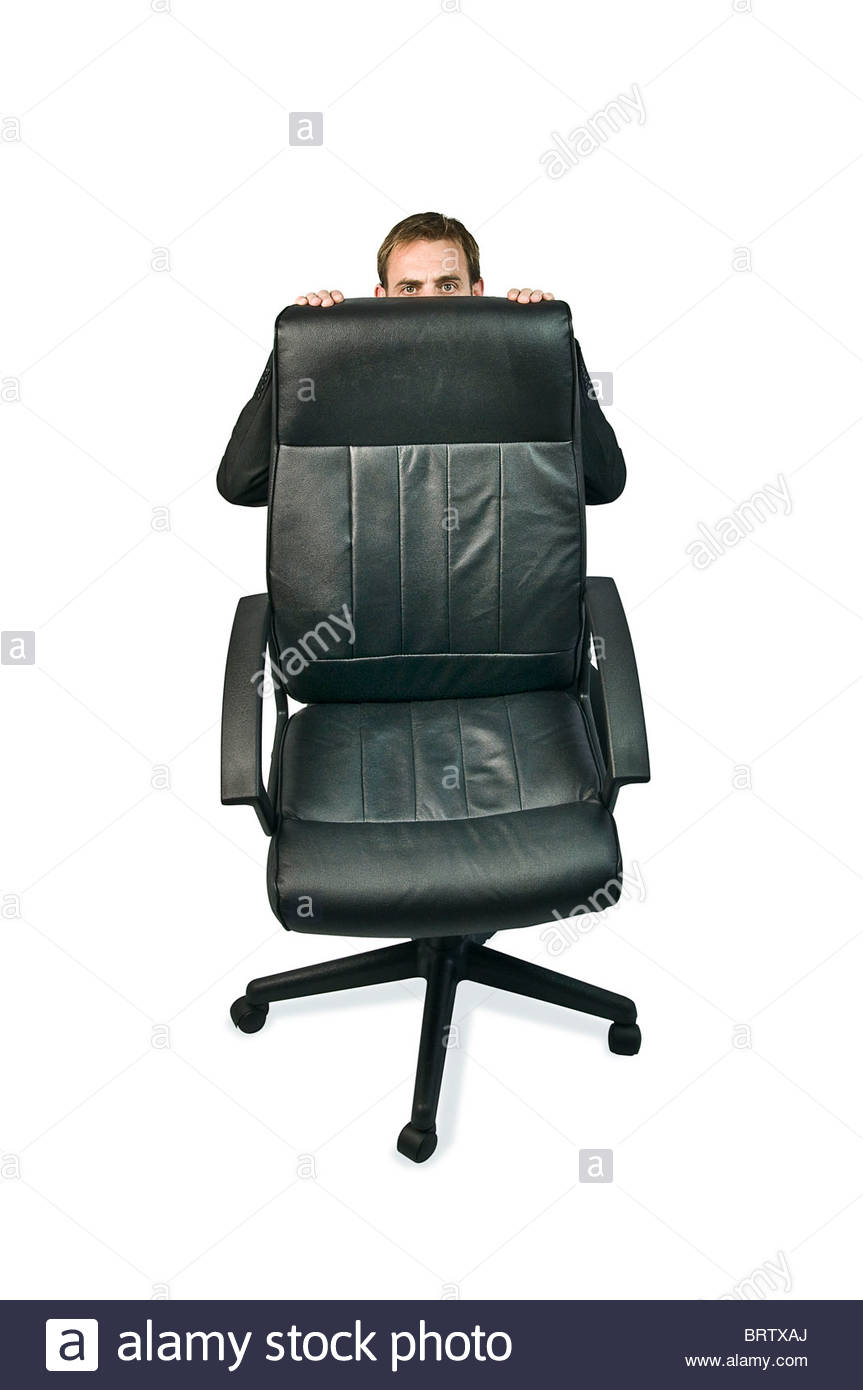business man Hiding behind office chair - Stock Image