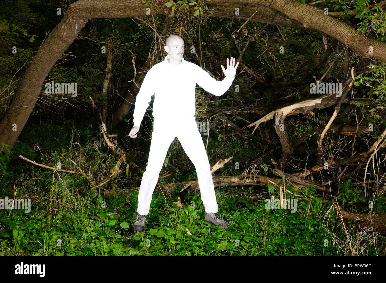 Floating alien man in bright white clothes caught in a thick overgrown forest - Stock Image