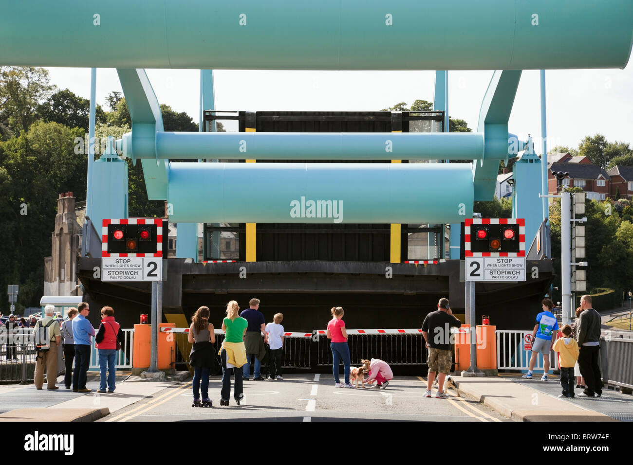 Red stop lights and barriers on tidal Barrage bascule swing bridge with people waiting to cross. Cardiff Bay, South - Stock Image