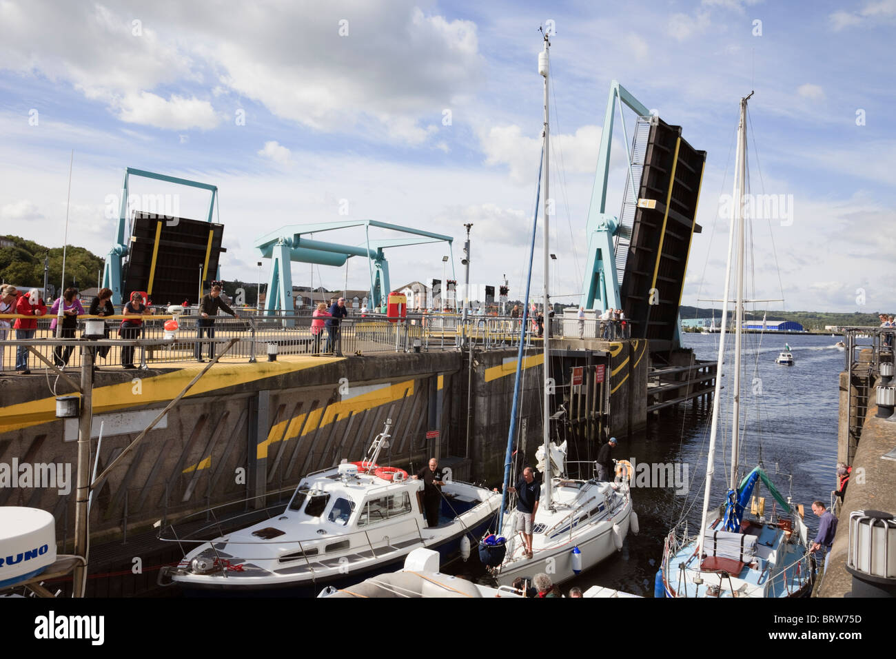 Cardiff Bay, Glamorgan, South Wales, UK. Tidal barrage bascule bridges open to let boats into navigation lock from - Stock Image