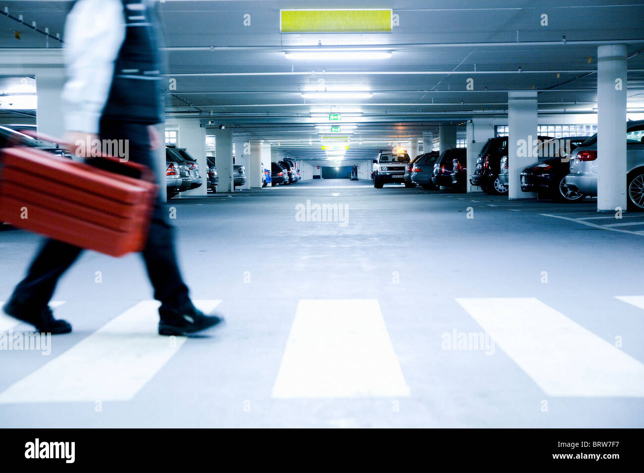 Workman on a zebra-crossing in an underground carpark - Stock Image