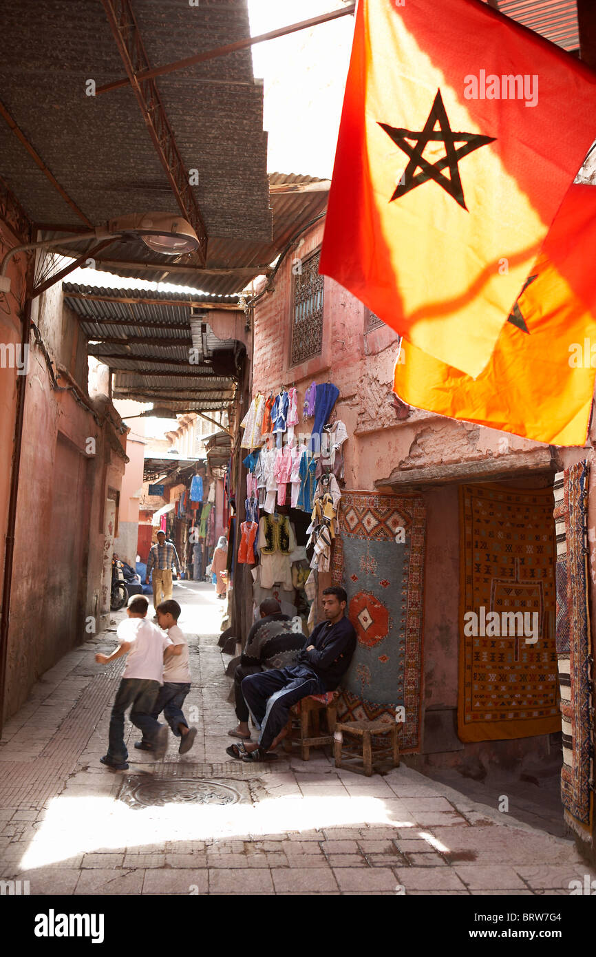 MARRAKESH: CHILDREN RUNNING IN NARROW STREET IN SOUK - Stock Image