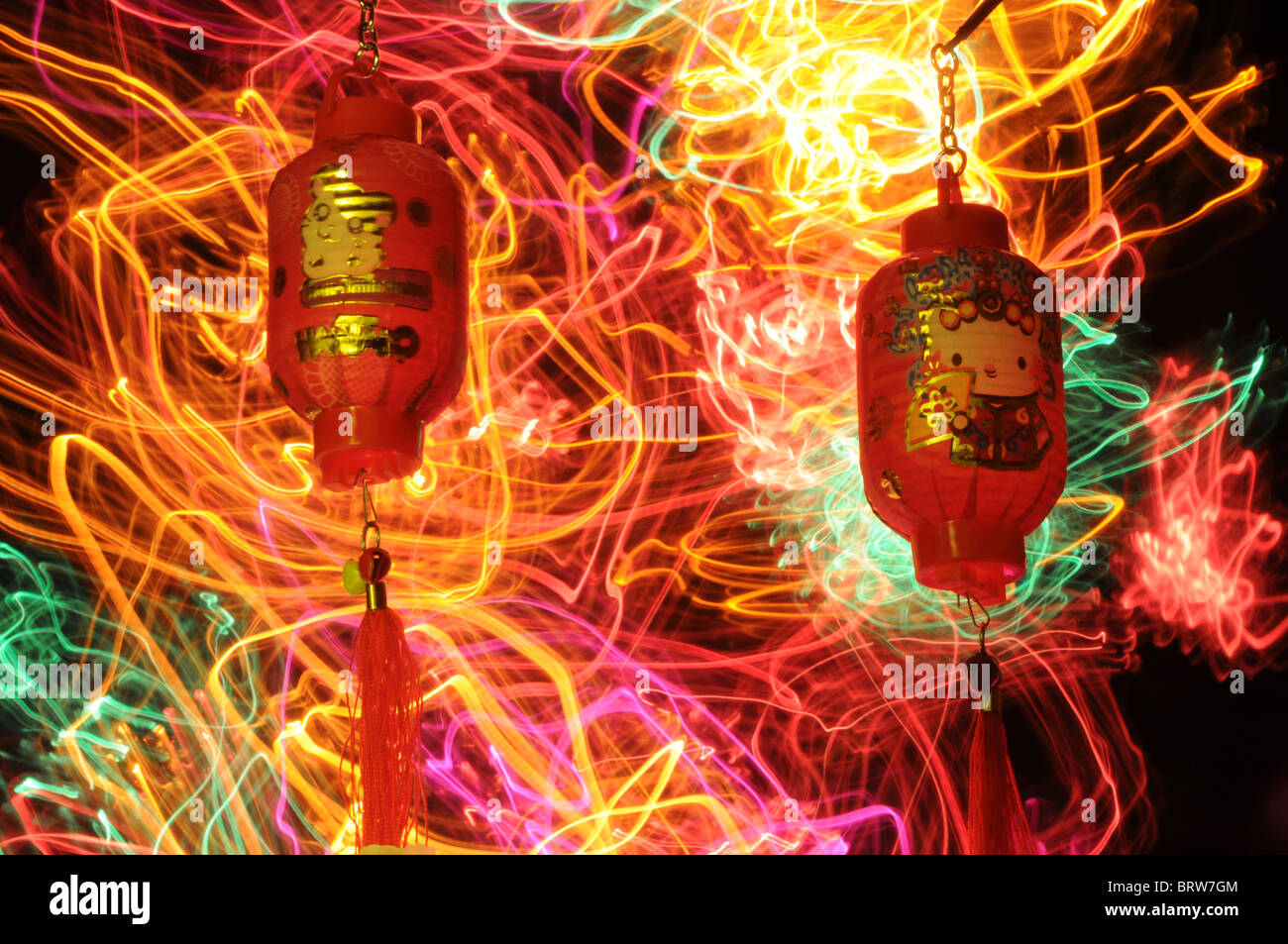 Chinese new year celebrations with lantern and bright swirling colorful movement of vibrant lights behind - Stock Image
