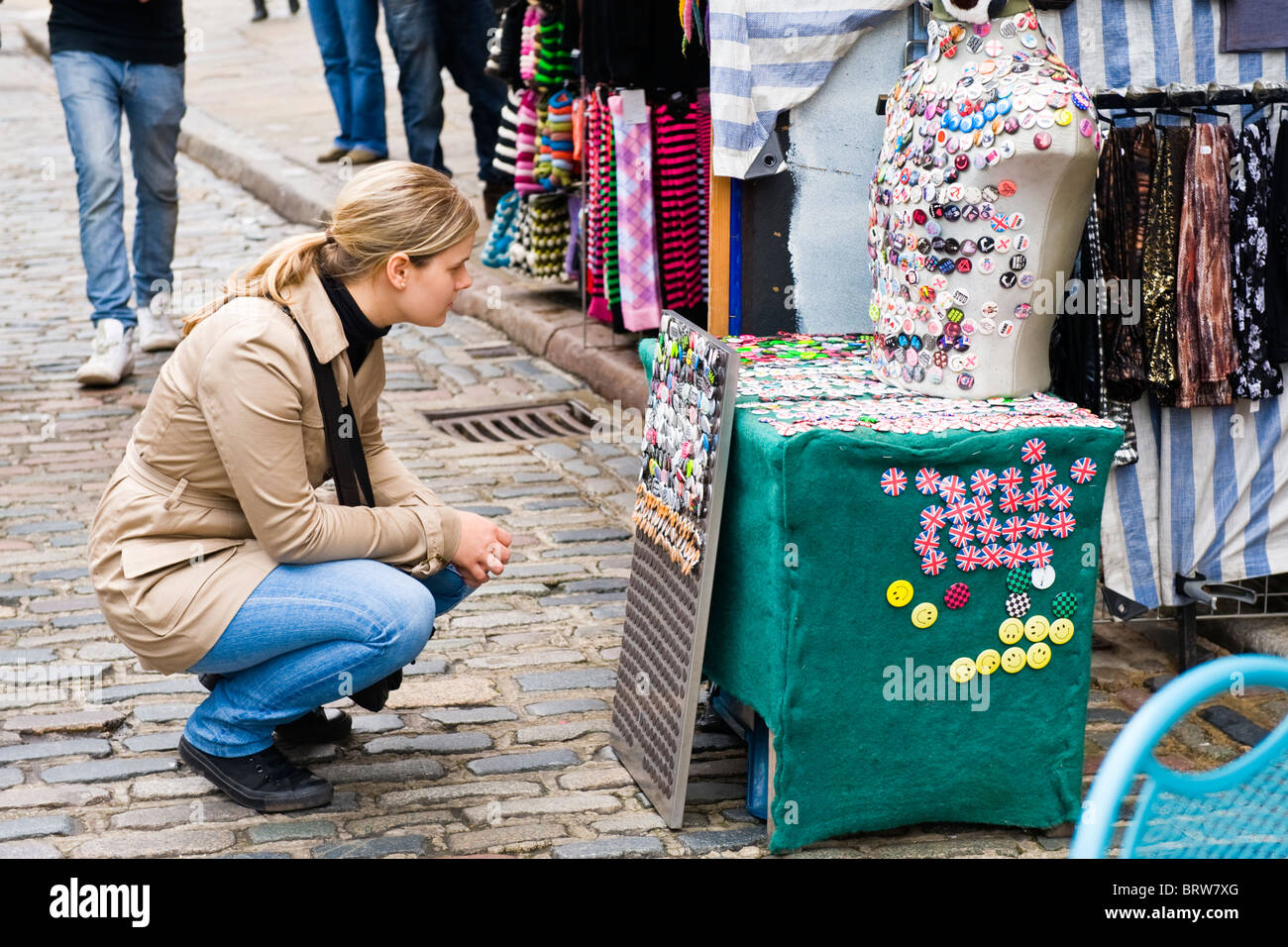 Camden Town Market Lock , pretty young blond girl in leather jacket & jeans crouches by display of selecting of Stock Photo