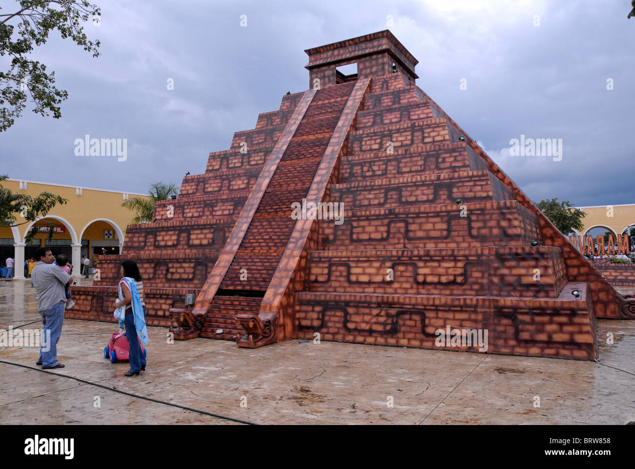 Xmatkuil, Yucatan / Mexico - November 12: A family stands by a replica of the Chichen Itza pyramid at the Xmatkuil Stock Photo