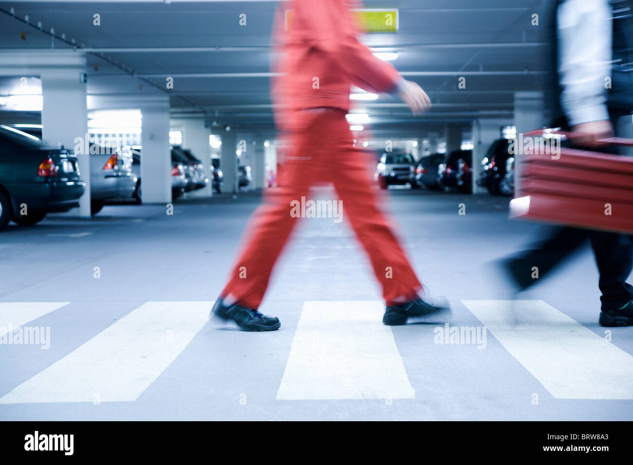 Workmen on a zebra-crossing in an underground carpark - Stock Image