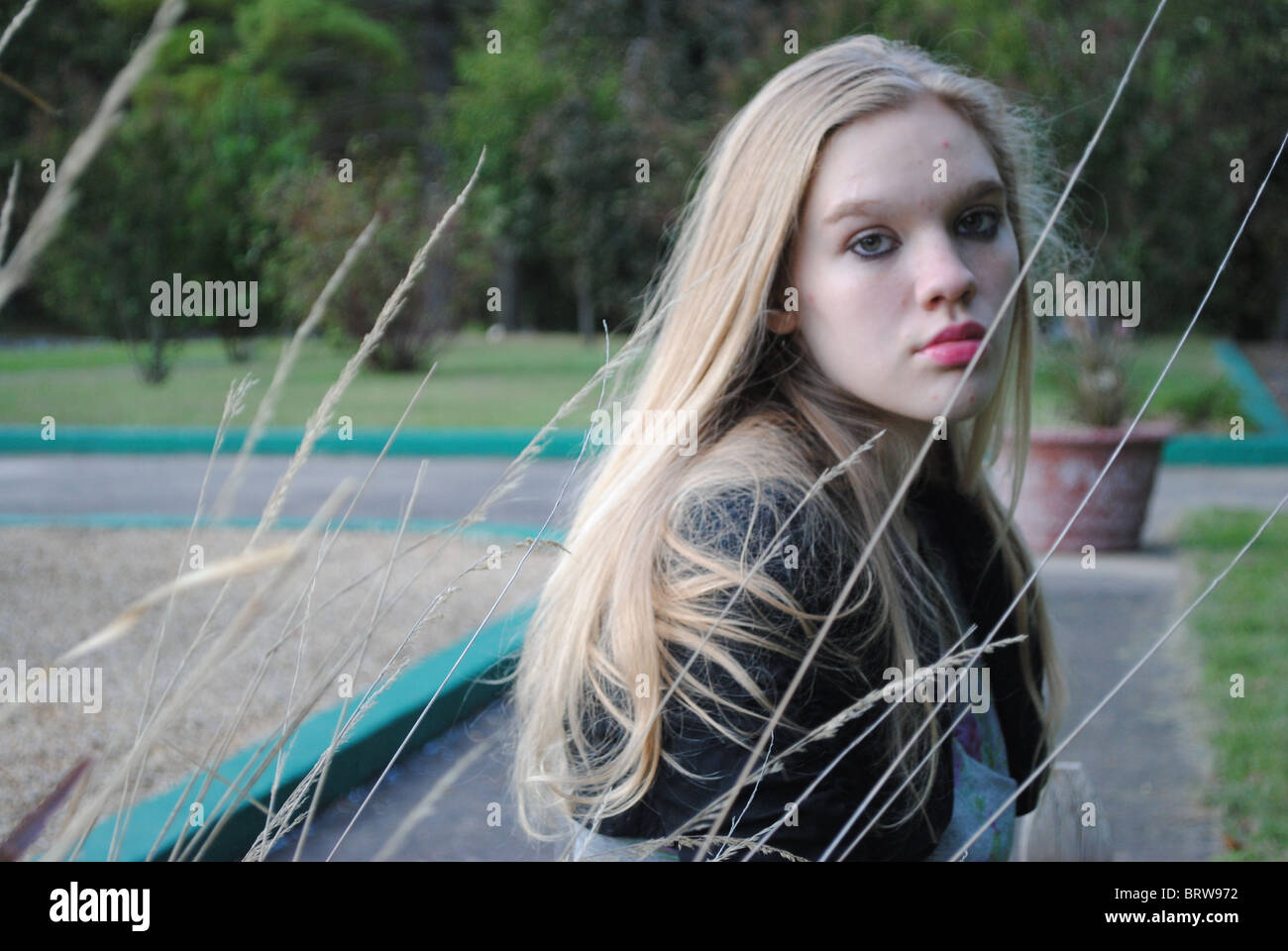 blonde girl reeds wheat outdoors park sullen contemplative - Stock Image