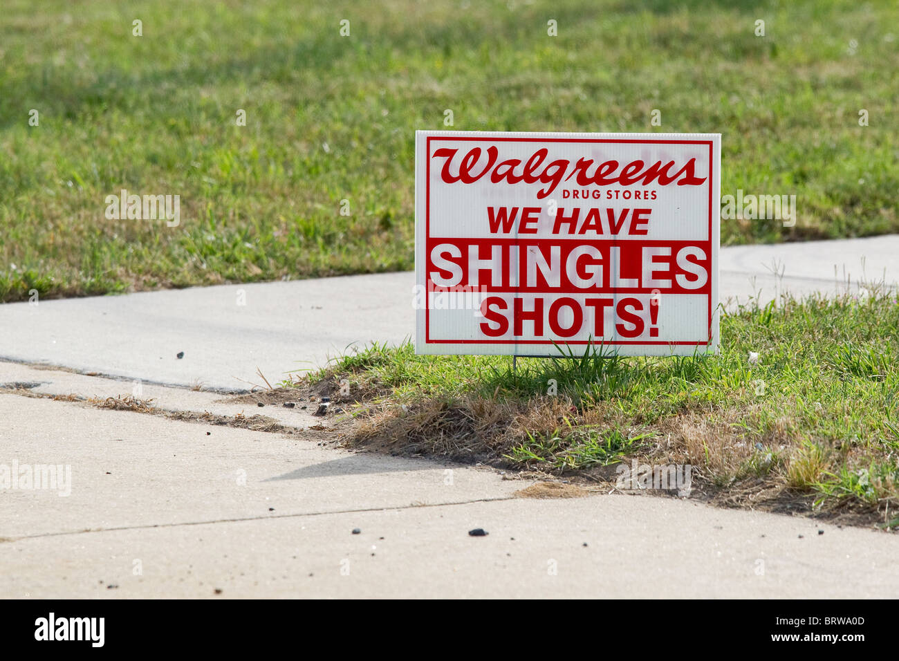 Small Walgreens sign advertising vaccines, shots for shingles, on grass next to sidewalk - Stock Image