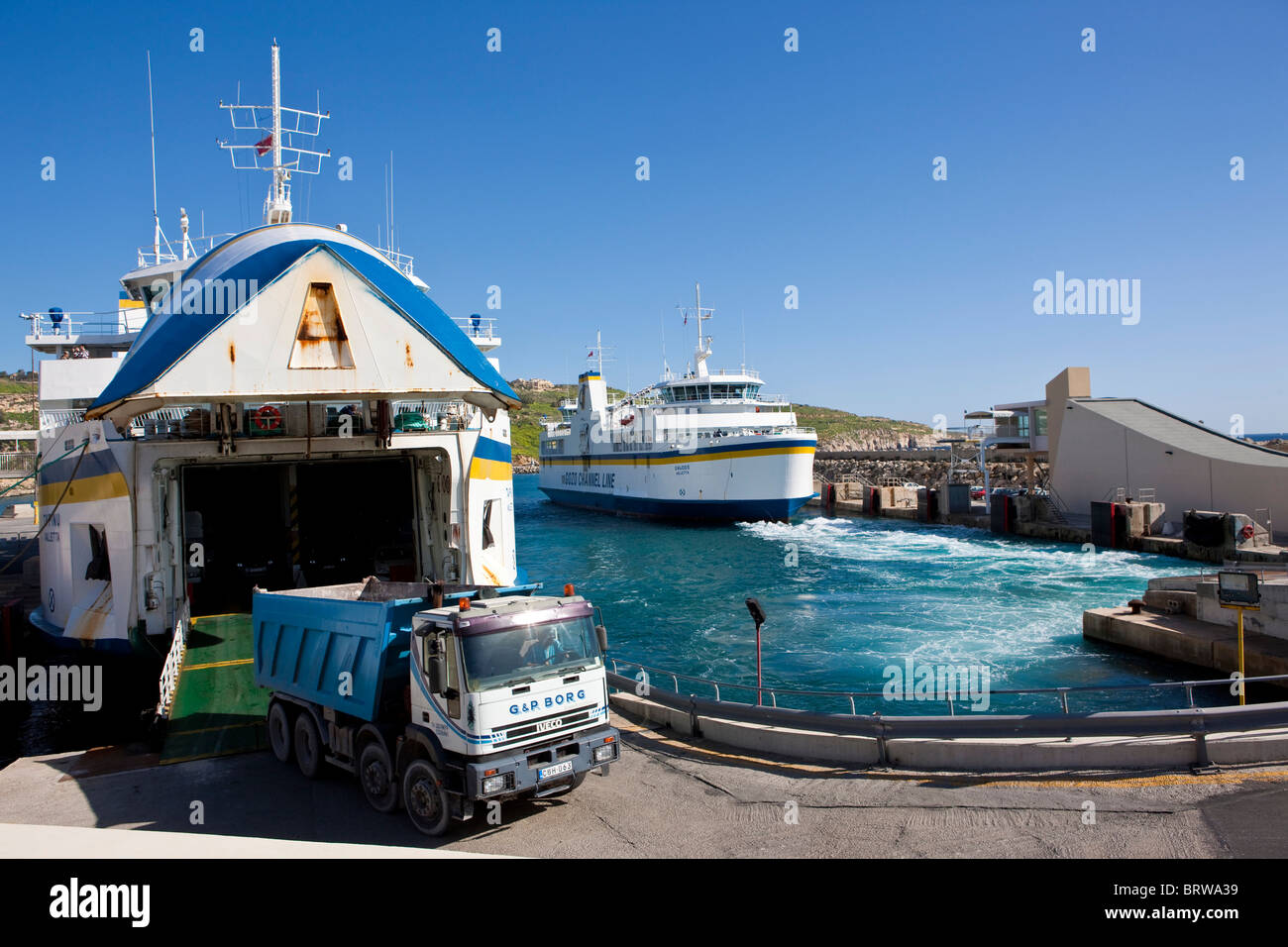 Ferry from Malta docking in the Mgarr port of Gozo and unloading a truck, Mgarr, Gozo, Malta, Europe - Stock Image