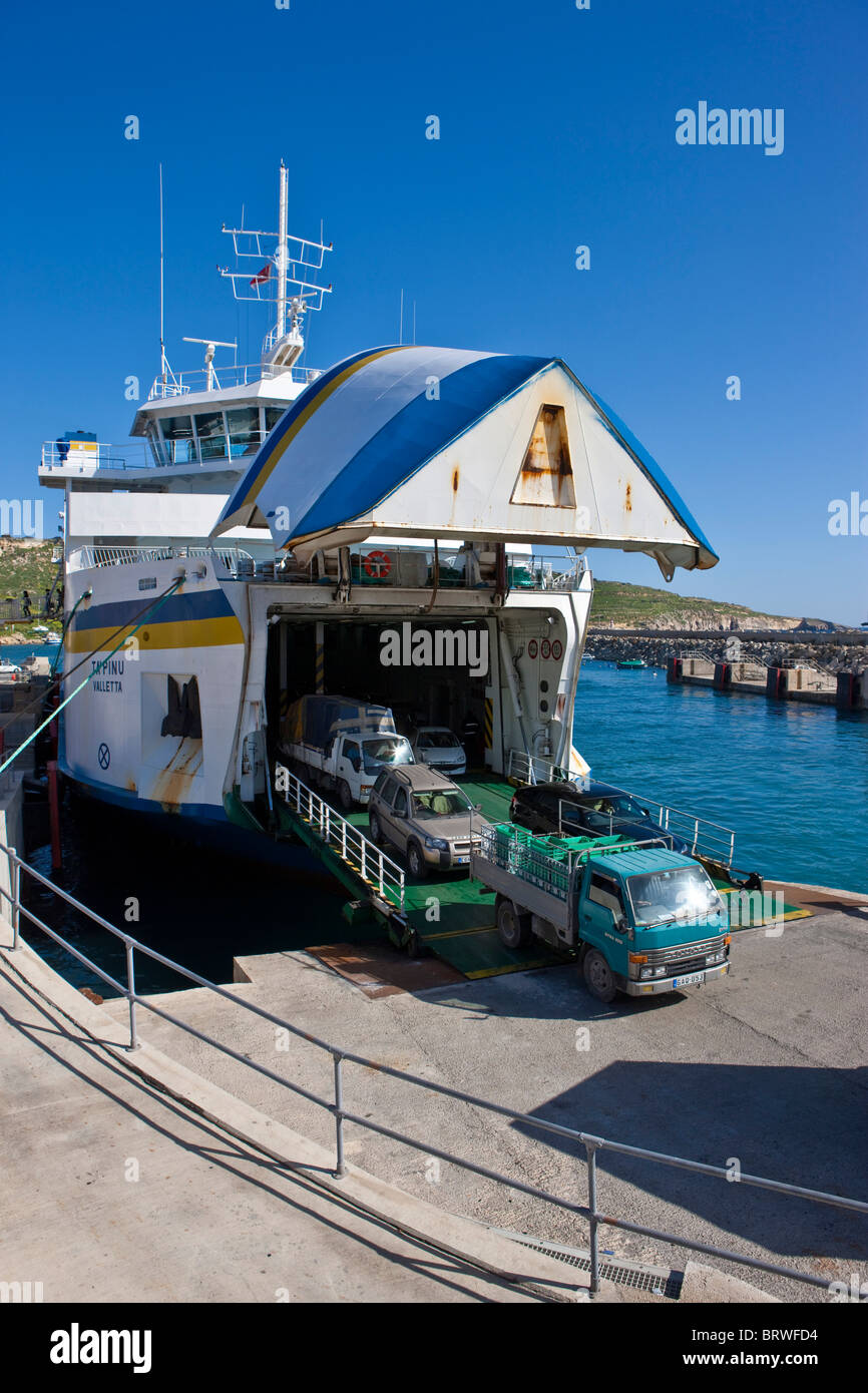 Ferry from Malta docking in the Mgarr port of Gozo and unloading vehicles, Mgarr, Gozo, Malta, Europe - Stock Image