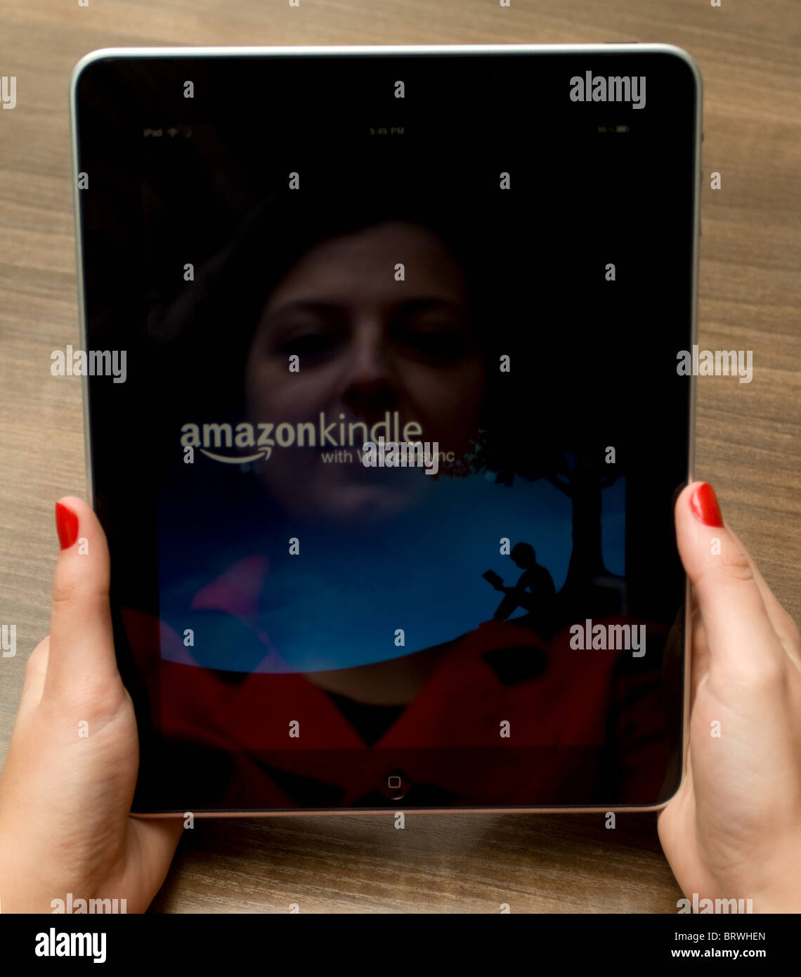 Woman's hands holding an Apple iPad with her reflection in