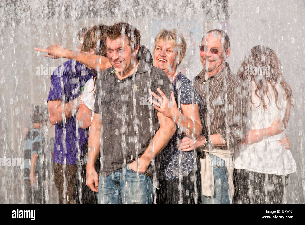 COUPLE OF ADULT ENJOYING THE GOOD WEATHER UNDER THE FOUNTAIN HAVING FUN - Stock Image