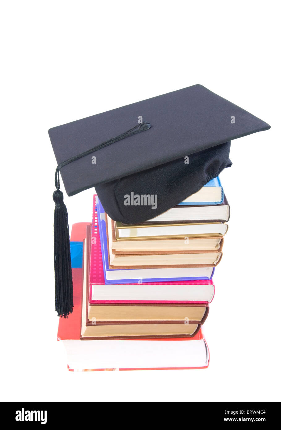 Student hat on a tower made of books, against a white background - Education concept - Stock Image