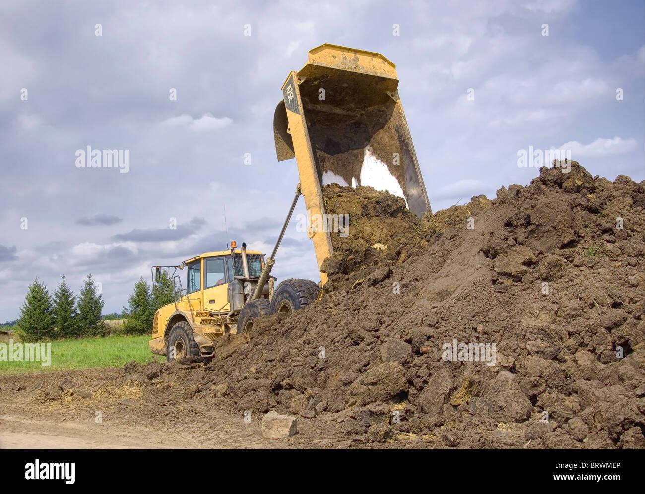 Heavy duty dump truck dumping soil - Stock Image