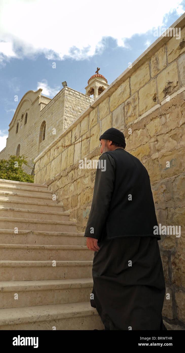 SYRIA Bishop Christo climbing the stairs of his Saint George's monastery, Almishtaya, Wadi al-Nasarah, Valley - Stock Image