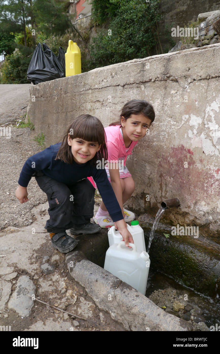 SYRIA Children collecting spring water, village of Alkaimi,Wadi al-Nasarah, 'Valley of the Christians', - Stock Image