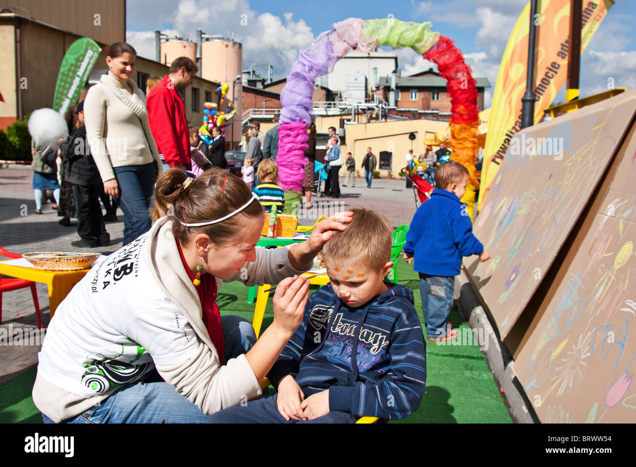 A woman painting boy face - Stock Image
