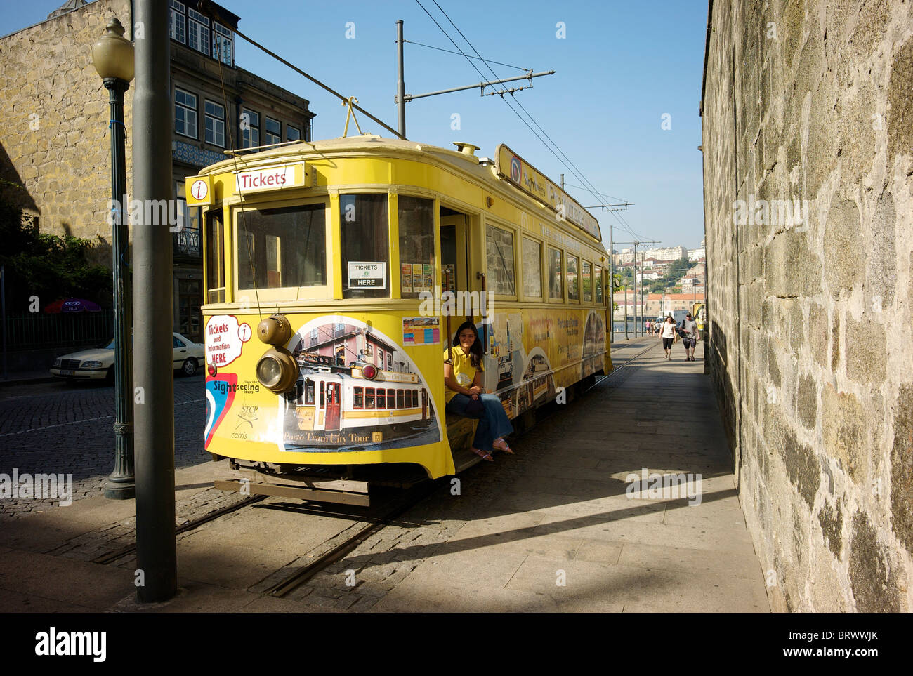 Ticket sales girl sits on the steps of a yellow tram which is used as the ticket sales office in Porto. Stock Photo