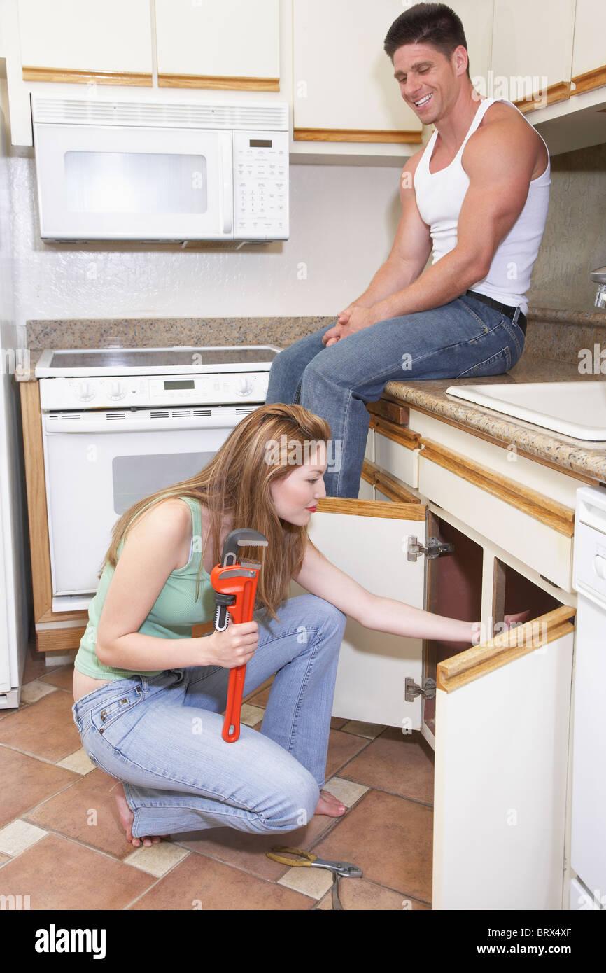 Man watching female plumber fixing kitchen sink Stock Photo ...