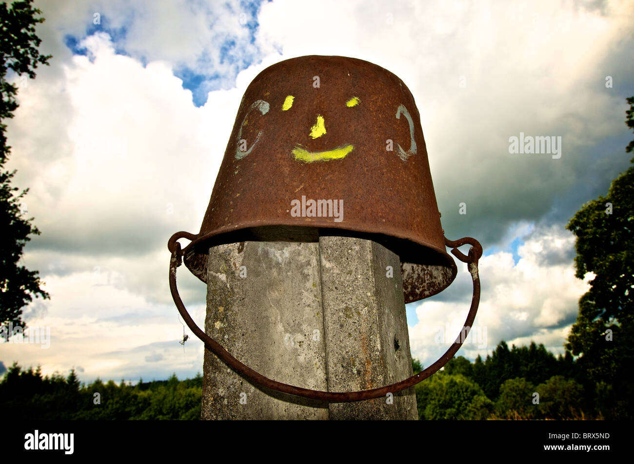 Upended bucket with smiley face. - Stock Image