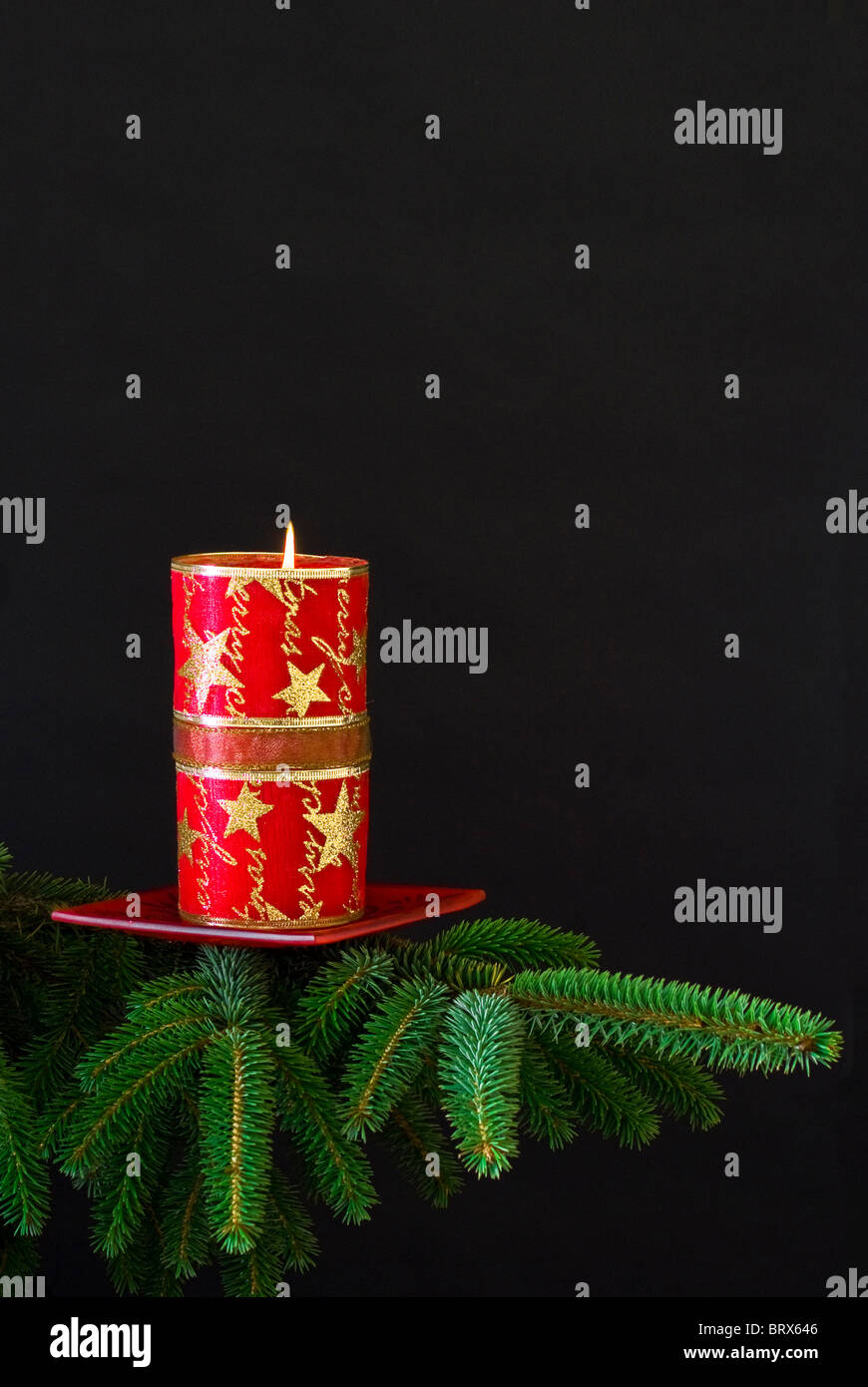 Red Christmas candle on spruce branch - black background - Stock Image