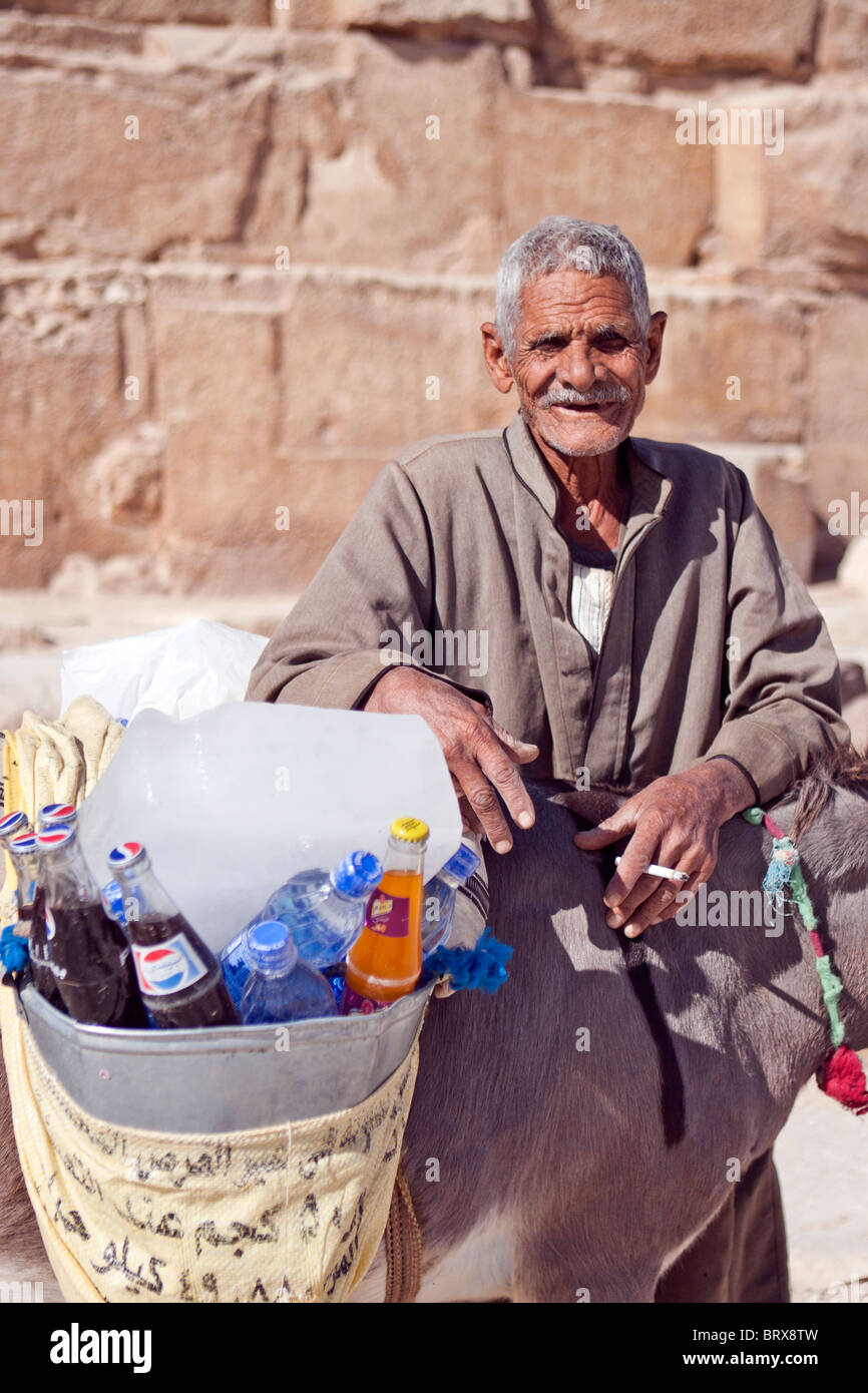Elderly Egyptian man selling refreshments at the base of the Great Pyramid, Giza, Egypt. Stock Photo