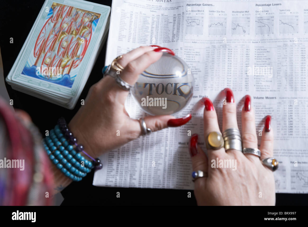 Fortune teller looking at newspaper financial pages through crystal ball, close-up of hands - Stock Image