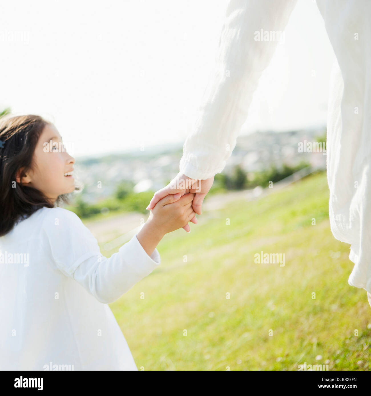 Young Girl Holding Mother's Hand and Walking in Field Stock Photo