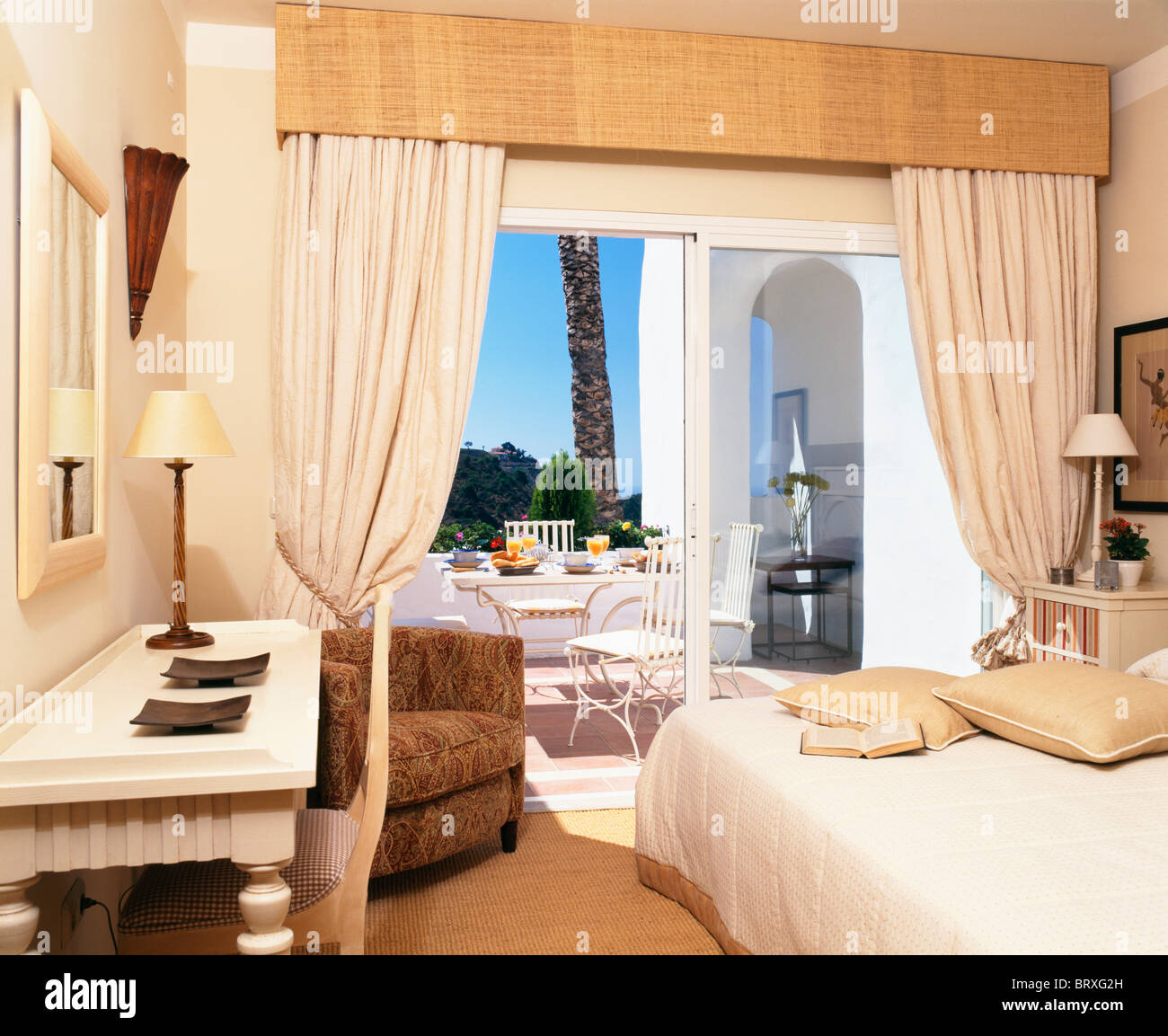 Spanish apartment bedroom with white curtains at patio doors ...