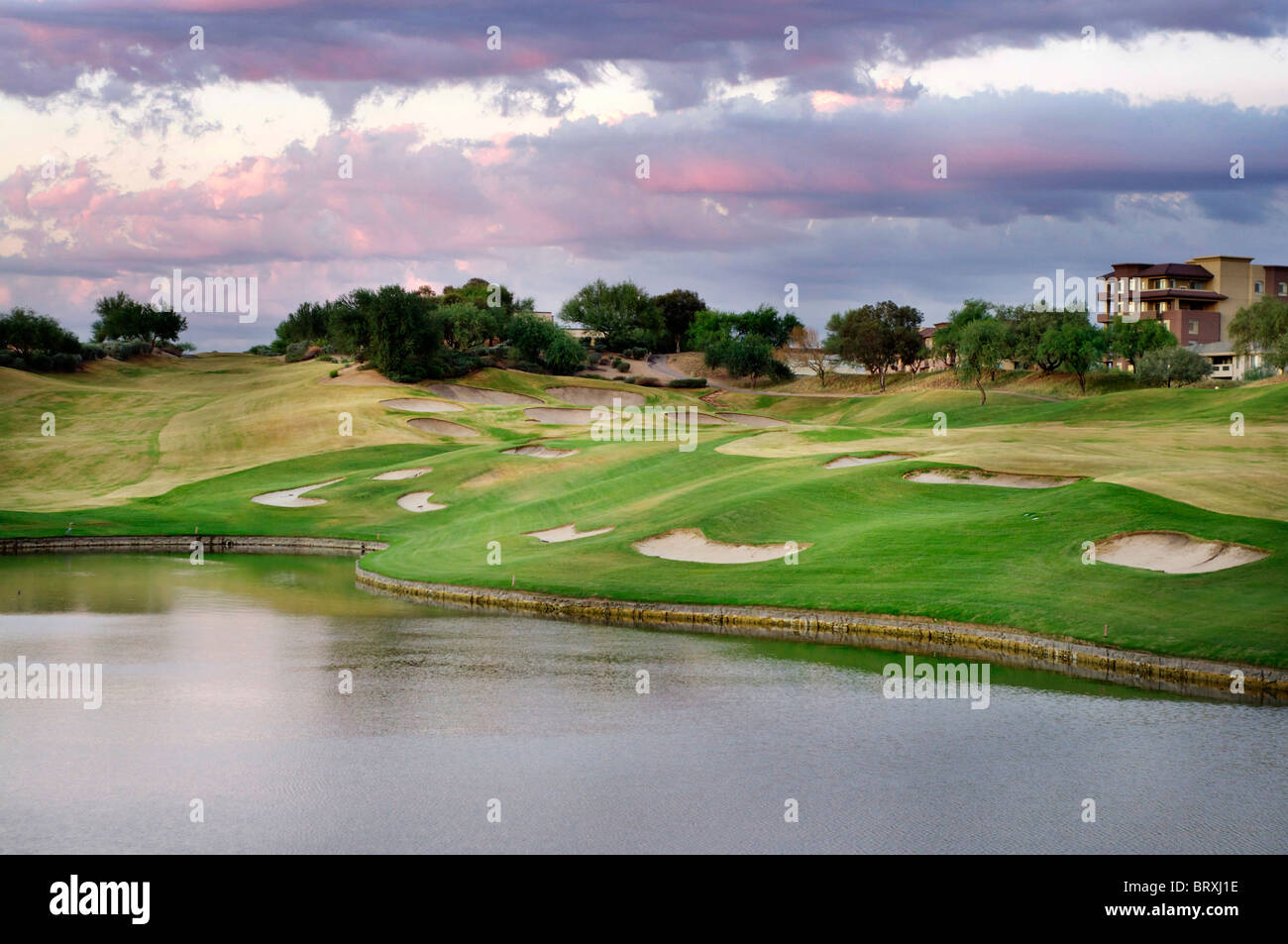 Photo of beautiful golf course with lake in foreground and sunset sky located in Scottsdale,AZ - Stock Image